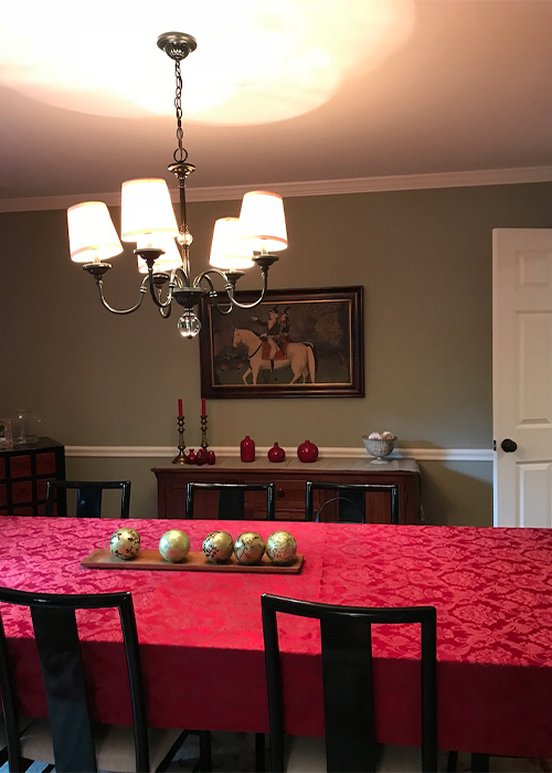 This dining room was revitalized with prominent gold and crystal sconces and chandelier as well as with a lighter wall color.  Further modernization was accomplished by using a beige fretwork fabric for the curtains.
